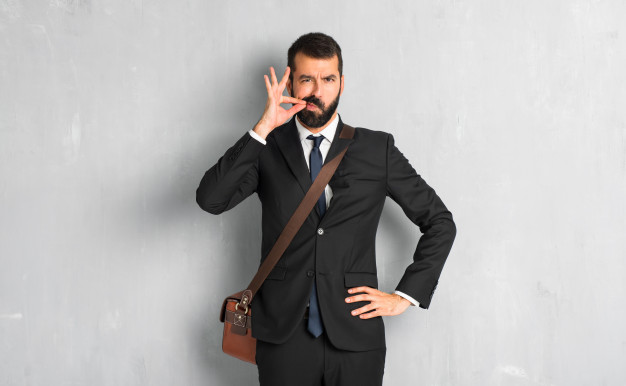 businessman-with-beard-showing-sign-closing-mouth-silence-gesture_1368-31002
