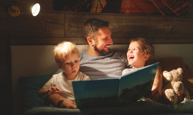 evening family reading. father reads children . book before going to bed