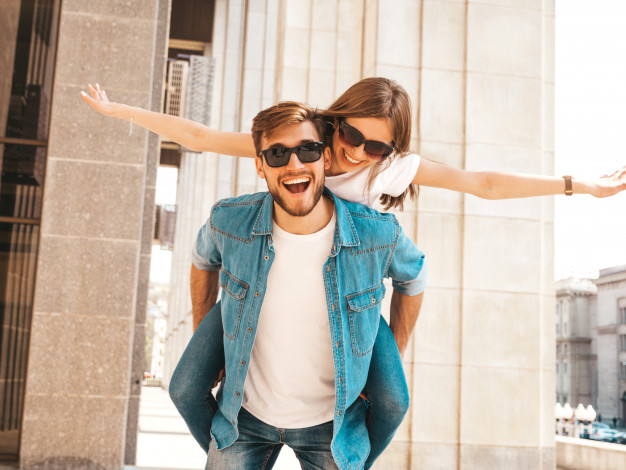 smiling-beautiful-girl-her-handsome-boyfriend-casual-summer-clothes-man-carrying-his-girlfriend-back-she-raising-her-hands_158538-5432