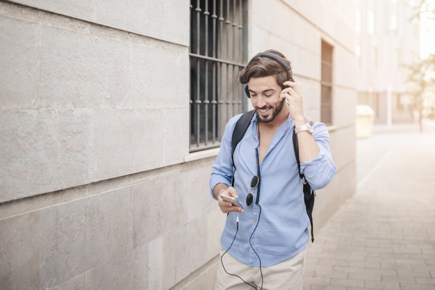 happy-man-walking-pavement-listening-music_23-2147860923