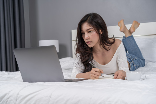 woman-writing-notebook-using-laptop-computer-bed_35076-2760