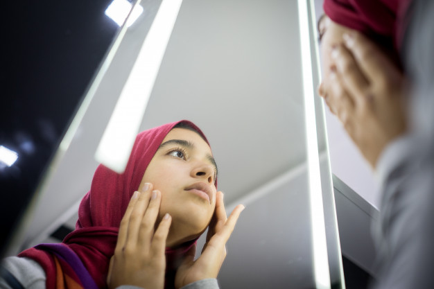 muslim-beautiful-girl-looking-into-mirror-checking-face-skin_21730-13509